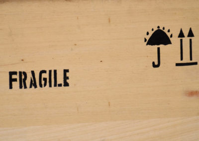 a wooden crate with the word fragile painted on the side