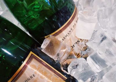 champagne bottles with shiny water resistant labels sitting in ice