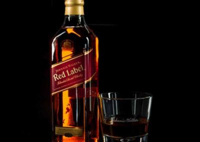 glass liquor bottle showing red label with gold letters